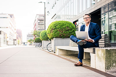 Mature businessman using laptop on bench outdoors - p300m2004532 von Joseffson
