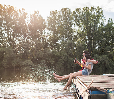 Happy young couple having a drink and splashing with water on jetty at a remote lake - p300m2114940 by Uwe Umstätter