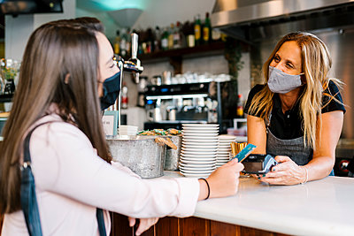 Businesswoman in face mask paying through credit card at counter in cafe during COVID-19 crisis - p300m2220718 by Ezequiel Giménez