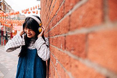 Cheerful young woman wearing headphones by brick wall - p300m2298827 von Angel Santana Garcia