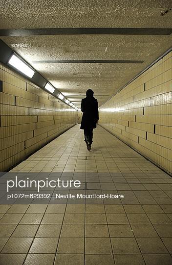 Figure walking away down an underground tunnel - p1072m829392 by Neville Mountford-Hoare