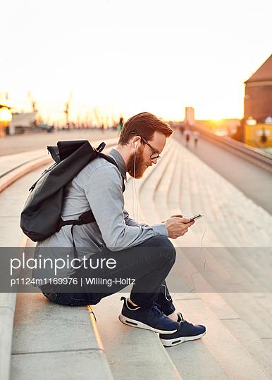 Mann mit Kopfhörern und Smartphone - p1124m1169976 von Willing-Holtz