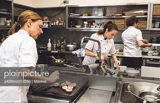 Female chefs preparing food in commercial kitchen at restaurant - p426m2212250 by Maskot