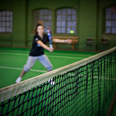 Teenage girl playing tennis with focus on the net in foreground - p1025m788495f by Mujo Korach