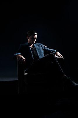 Man in blazer sitting on armchair - p1248m2206129 by miguel sobreira