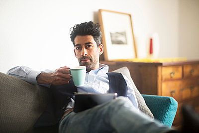 Portrait of pensive man with coffee mug and tablet sitting on couch at home - p300m1563112 by Sigrid Gombert