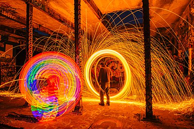 Man creating multi-color and golden spark light trails in derelict building - p429m1103272 by Pete Saloutos
