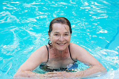 Senior woman in a pool - p975m2063287 by Hayden Verry