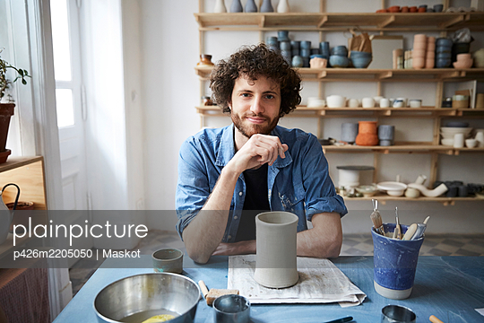 Portrait of mid adult man sitting in pottery class - p426m2205050 by Maskot