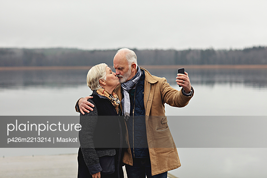 Senior couple kissing while taking selfie by lake against clear sky - p426m2213214 by Maskot