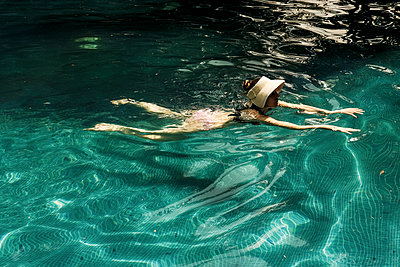 white woman with hut pool refreshing after jogging - p1166m2136909 by Cavan Images