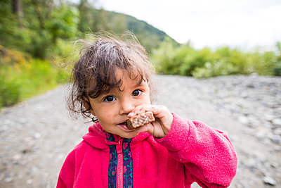 Girl eating chocolate bar while hiking - p1166m2201990 by Christopher Kimmel / Alpine Edge Photography