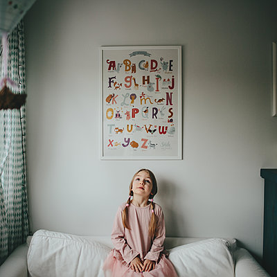 Girl sitting on sofa in kids room - p1414m1590577 by Dasha Pears