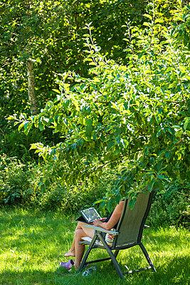 Woman reading in shadow of a tree - p1418m2288280 by Jan Håkan Dahlström