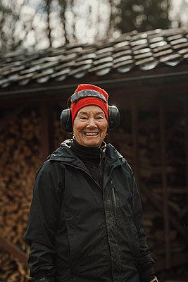 Smiling woman wearing ear protectors - p312m2191252 by Jennifer Nilsson