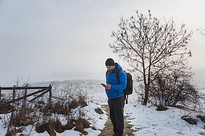 A man walking on a snowy trail - p352m1523757 by Calle Artmark