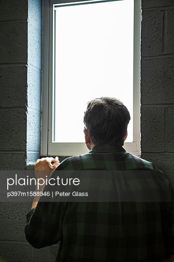 Ein Mann blickt aus einem Fenster - p397m1588946 von Peter Glass