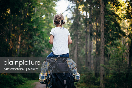 Rear view of father carrying daughter on shoulder while walking in forest - p426m2213245 by Maskot
