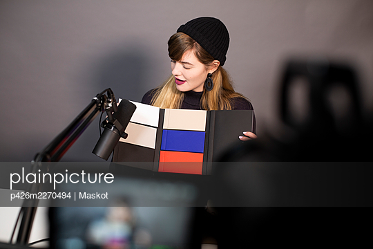 Businesswoman looking at product while recording through television camera - p426m2270494 by Maskot