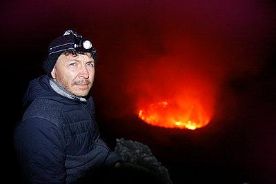 Africa, Democratic Republic of Congo, Virunga National Park, Man sittiing over Nyiragongo volcano crater - p300m2004586 by realitybites