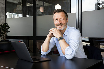 Businessman with hands clasped smiling while sitting at desk in office - p300m2287360 by Florian Küttler