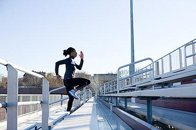 Woman running up grandstand - p3722406 by James Godman