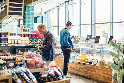 Men shopping in organic grocery store - p426m1407402 by Kentaroo Tryman