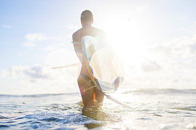 Rear view of woman carrying surfboard in sunlit sea, Nosara, Guanacaste Province, Costa Rica - p429m1407763 by dotdotred