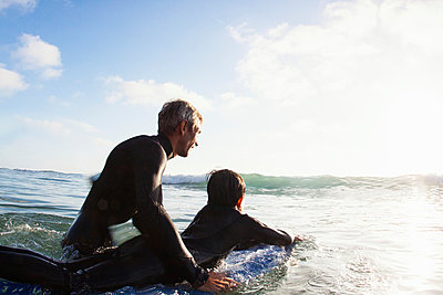 Father and son at sea with surfboard - p429m884148 by Yew! Images