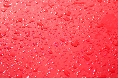 Drops on red surface - p4903383 by Tobias Thomassetti