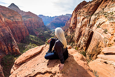 Caucasian woman sitting on rock admiring scenic view of rock formations - p555m1482096 by Steve Smith