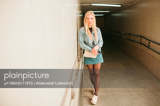 Full length portrait of young woman standing in underground walkway - p1166m2111973 by Aliaksandr Liulkovich