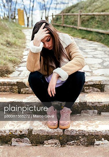 plainpicture - plainpicture p300m1568272 - Sad young woman sitting out... - plainpicture/Westend61/Marco Govel