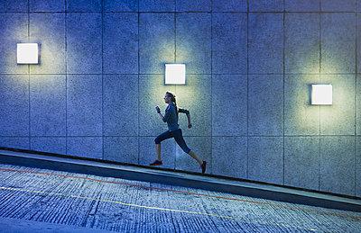 Female runner running ascending illuminated urban ramp - p1023m1201837 by Ryan Lees