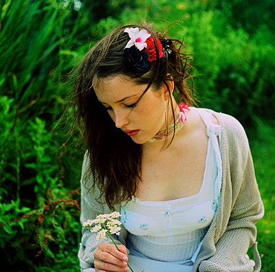 Woman gazing at wild flowers in a garden - p1072m829538 by Tracy Jean Shields
