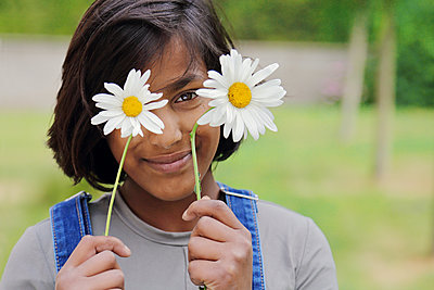 Young indian girl holding two daisys - p1540m2108982 by Marie Tercafs