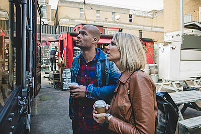 Couple holding disposable coffee shop standing outside store - p426m1442710 by Maskot