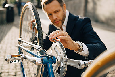Businessman repairing bicycle chain in city on sunny day - p426m2145639 by Maskot