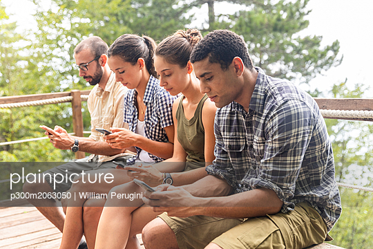Italy, Massa, hikers in the Alpi Apuane mountains looking at their smartphones and sitting on a bench - p300m2063050 by William Perugini