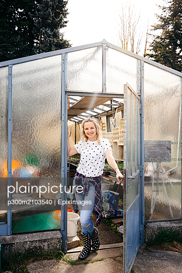 Young woman at doorway in greenhouse - p300m2103540 by Epiximages