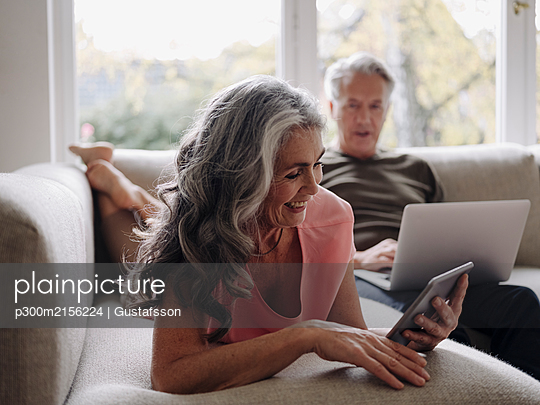 Senior couple relaxing on couch at home using tablet and laptop - p300m2156224 by Gustafsson