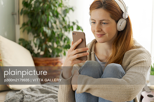 Young woman wearing headphones and using smartphone at home - p300m2179935 by VITTA GALLERY