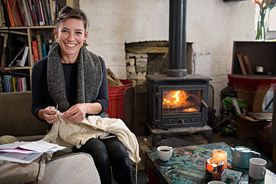Portrait smiling, confident woman knitting by fireplace in living room - p1023m2024508 by Tom Merton