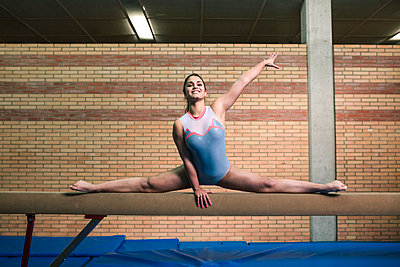 Full length of female gymnast with legs apart exercising on balance beam at gym - p1166m1576454 by Cavan Images
