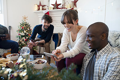 Millennial friends with smart phones in Christmas living room - p1192m2000138 by Hero Images