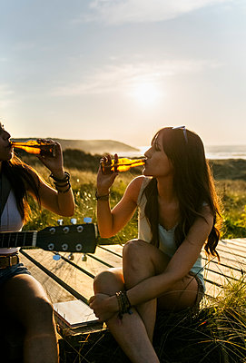 Two women with guitar drinking beer on boardwalk in dunes - p300m2114752 by Marco Govel