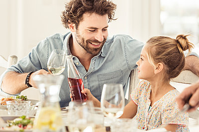 Father and daughter sitting at dining table toasting - p300m2167101 by Floco Images