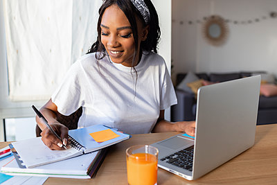 Smiling businesswoman writing while using laptop at home - p300m2286198 by Sus Pons