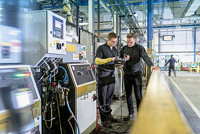 Apprentice engineers on production line in car factory - p429m1407974 by Monty Rakusen