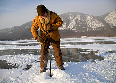 Undergoing preparations for fishing on frozen lake baikal in winter - p6521677 by Ken Scicluna